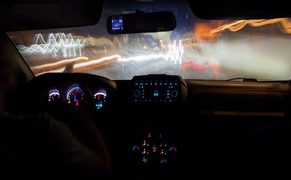 Driving a car in the city at night. Traveling on high speed, road lights defocused. View from inside with luminous dashboard